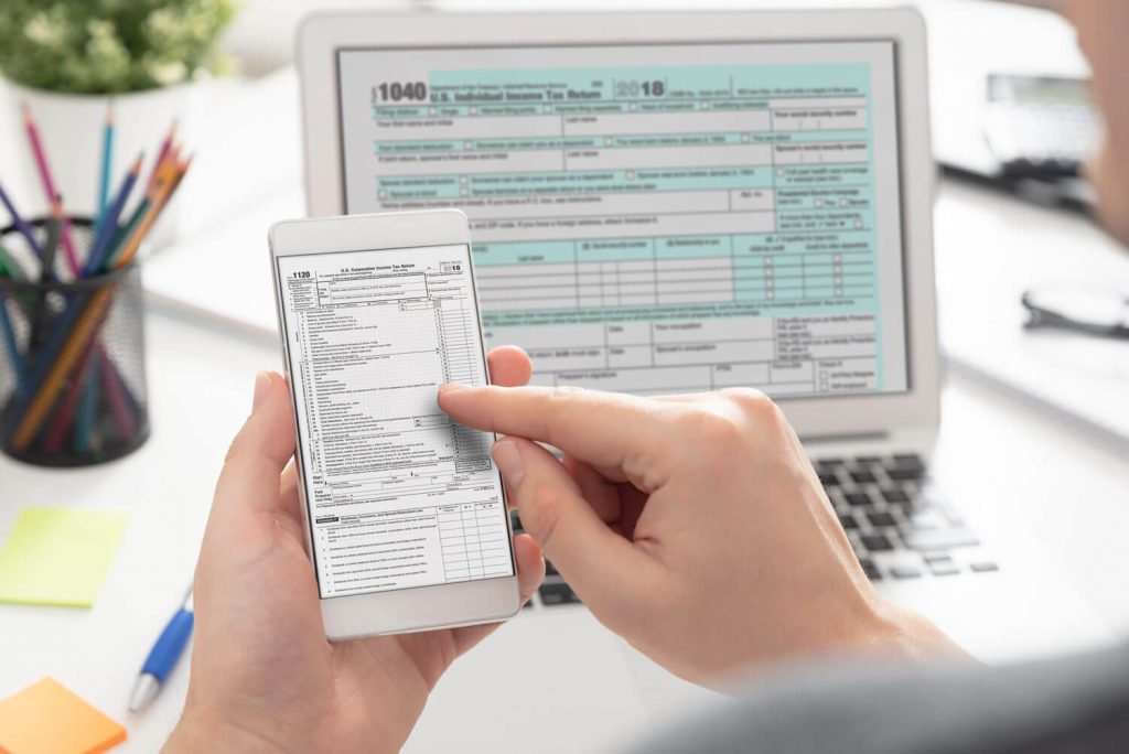 Accountant are filling online tax information using smartphone and laptop. Tax income concept